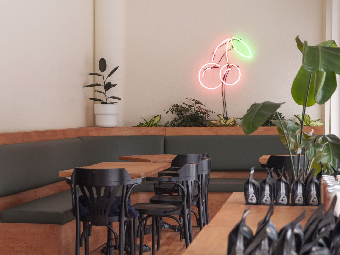 empty café with wood tables and black chairs and cherry neon sign
