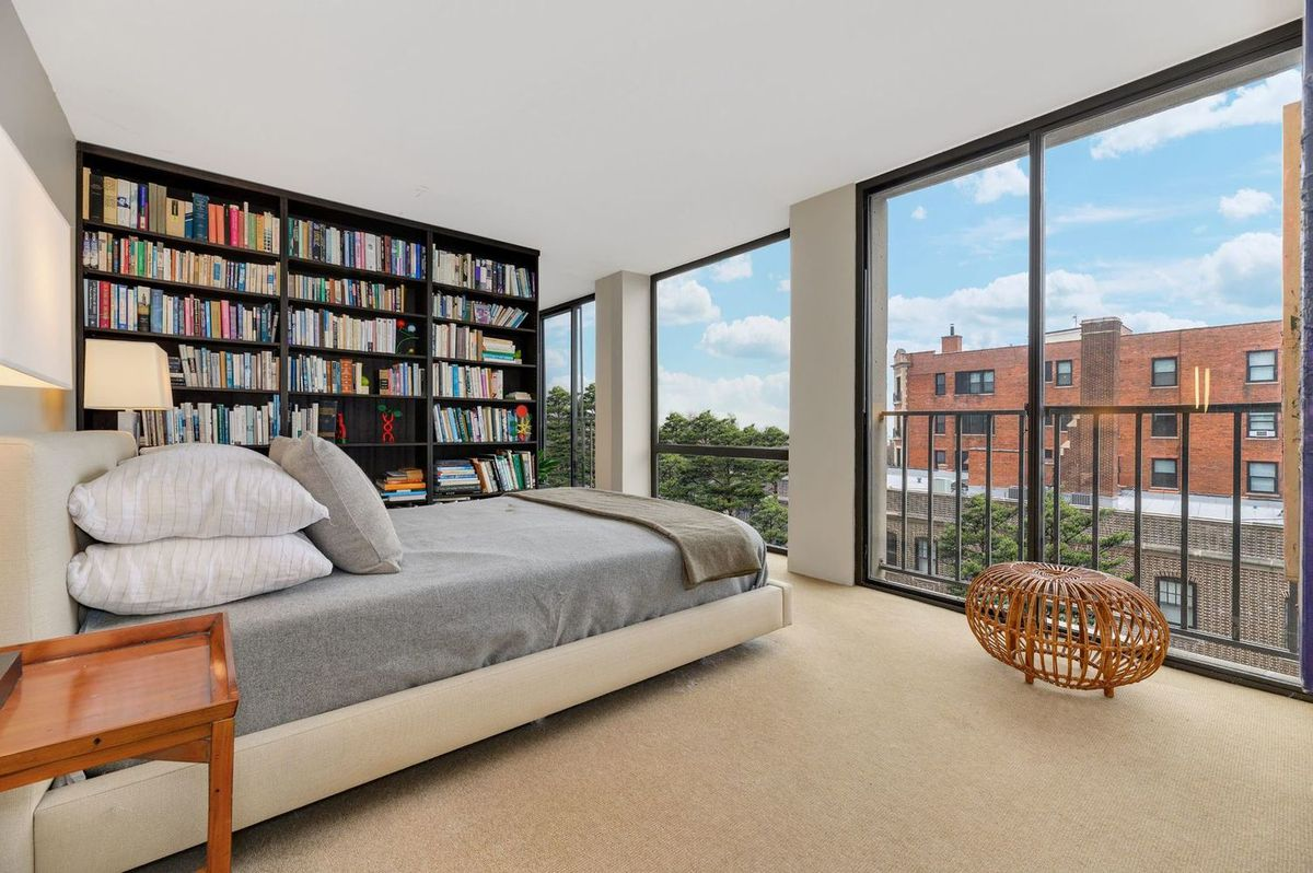 A bed faces floor-to-ceiling windows. There are night stands, table lamps, and a bookshelf wall.