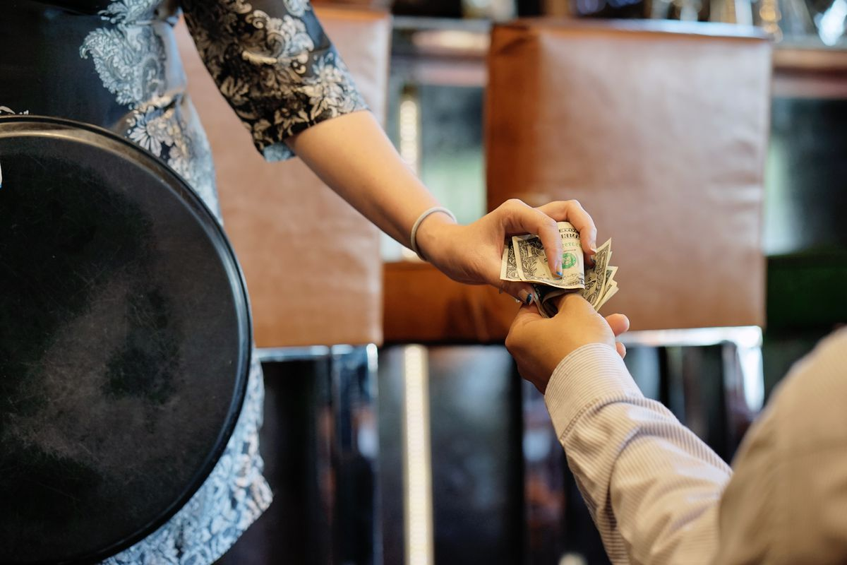 The hand of the waitress takes the tip. The waiter girl receives a tip from the client at the hotel bar. A bartender woman is happy to receive a tip at work. The concept of service