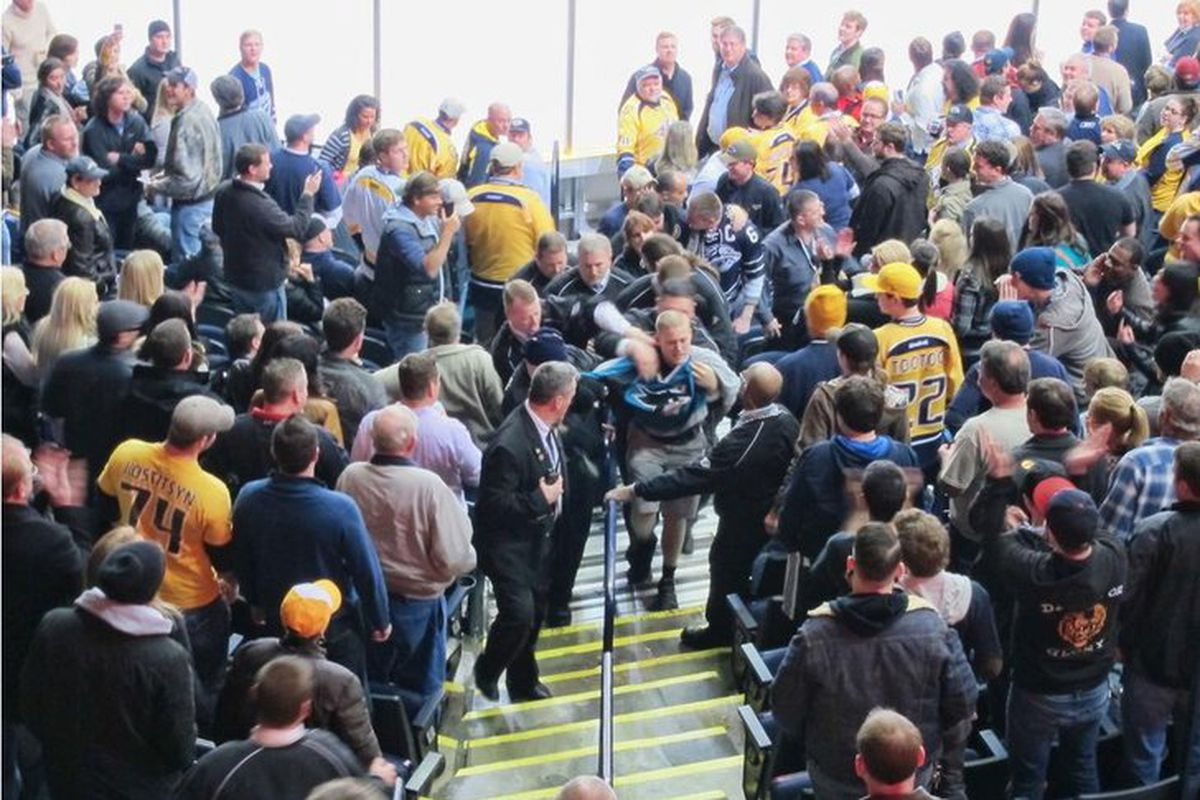 Bridgestone Arena security escorts the Sharks fan out of Section 114