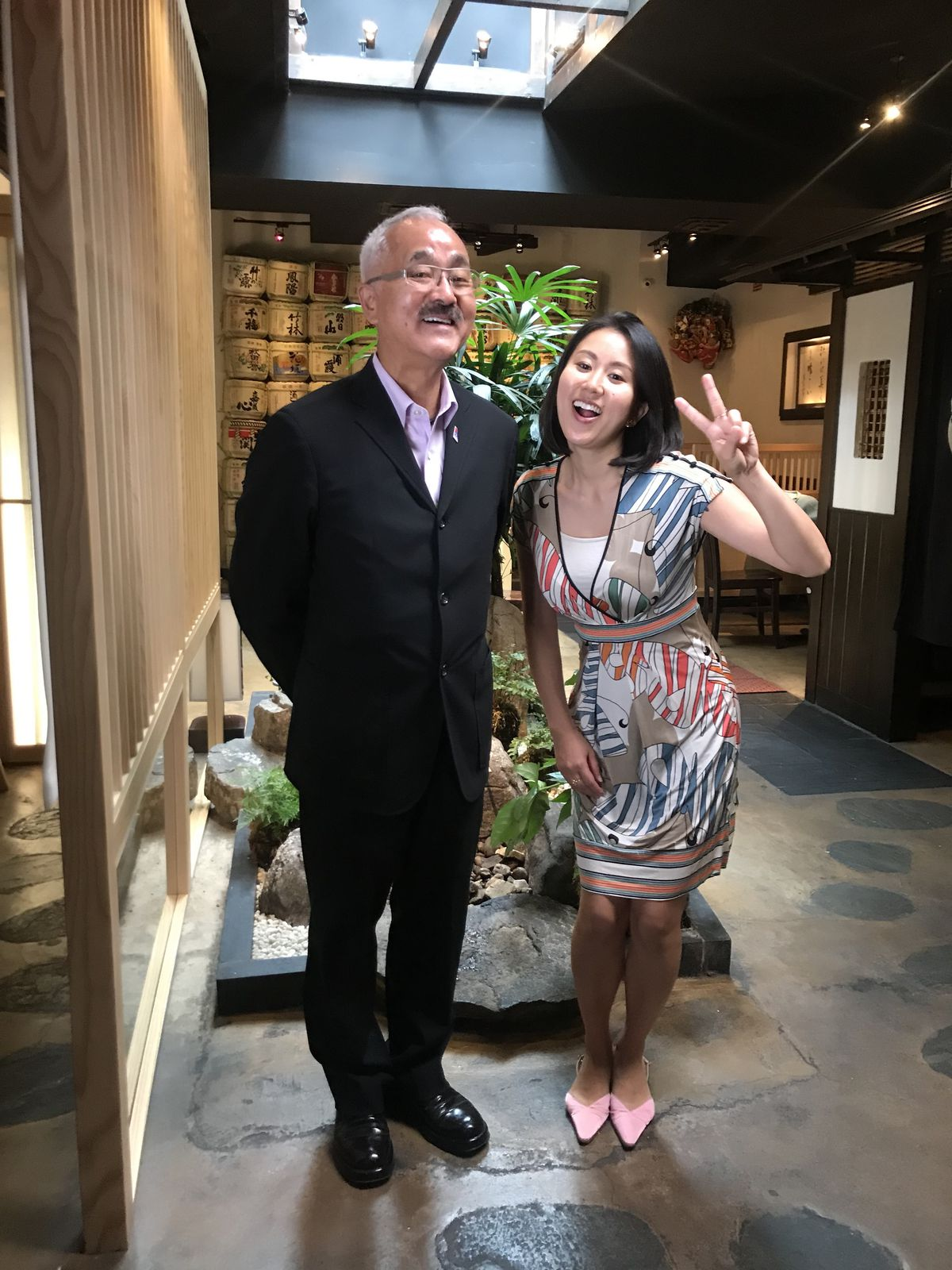 Bon Yagi and Sakura Yagi pose for a photo in front of an indoor Japanese garden
