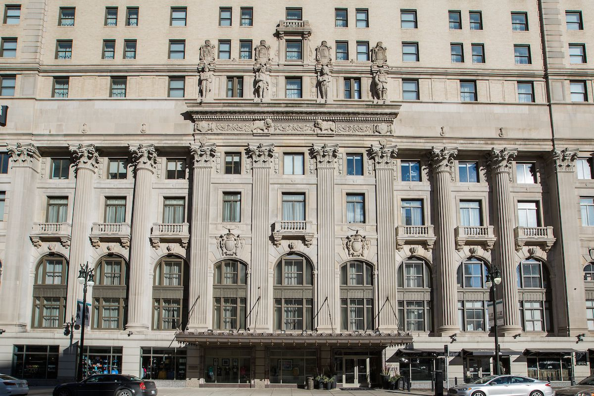 The exterior of the Westin Book Cadillac in Detroit. The facade is white with arched windows and statues.