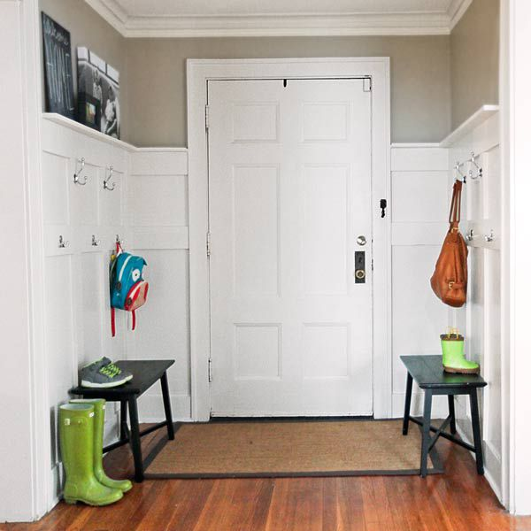 <p><strong>After:</strong> Two benches, 10 wall hooks, and a shallow ledge provide storage aplenty on a backdrop of classic double-panel wainscoting.</p>
