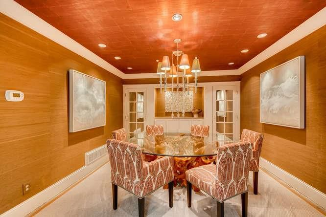 A small dining room coated in grasscloth with an orange ceiling.