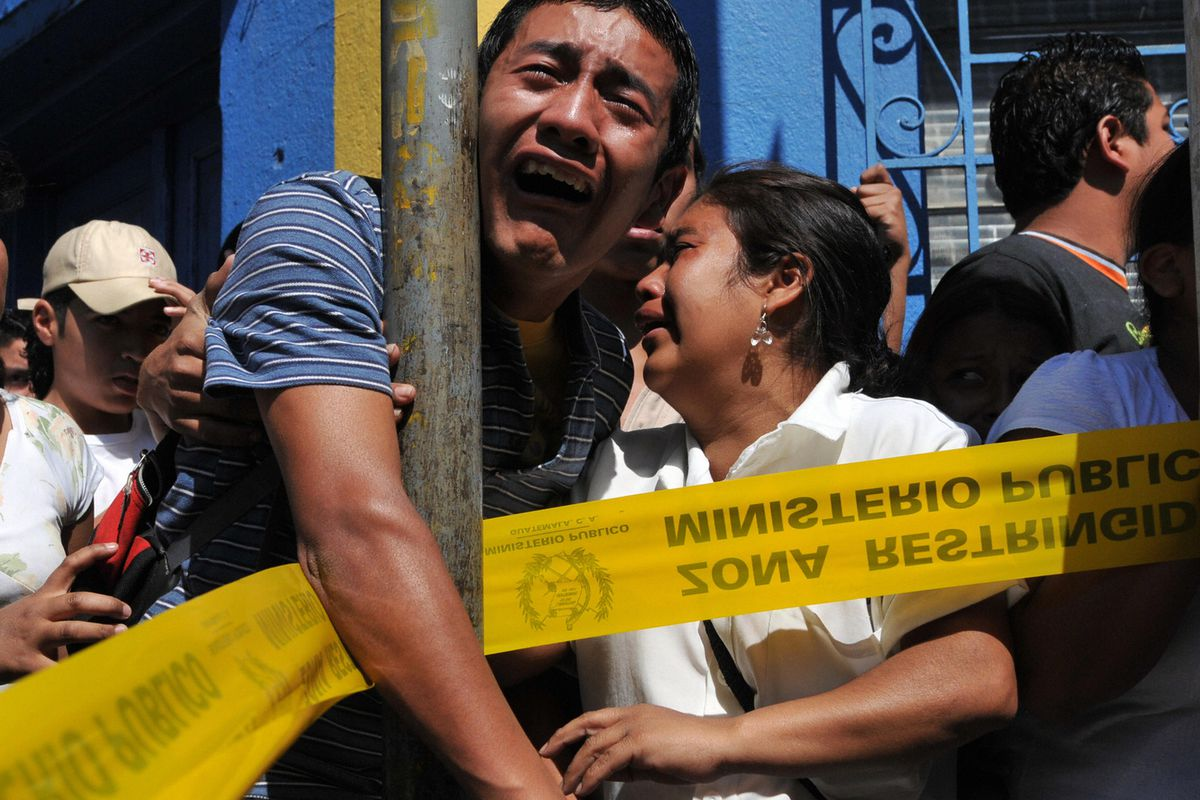 A man grieves for two murder victims in Guatemala.