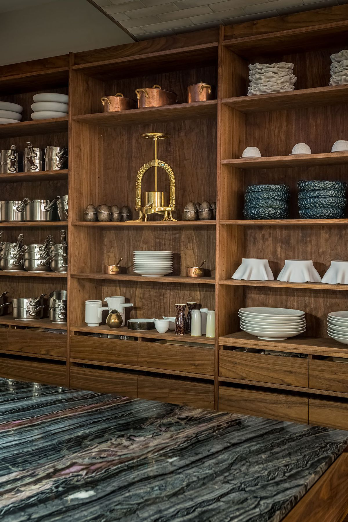 Fine dining plates and accoutrement sit on shelves.