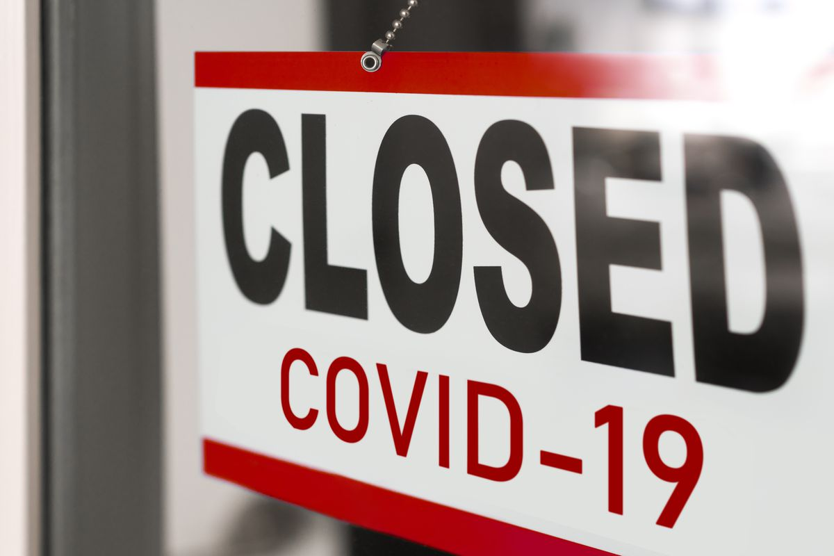 """A sign on a restaurant window says """"Closed COVID-19."""""""