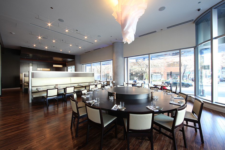 The bright interior or Urbane's dining room, with dark wood accents, a chandelier, and a hardwood floor.
