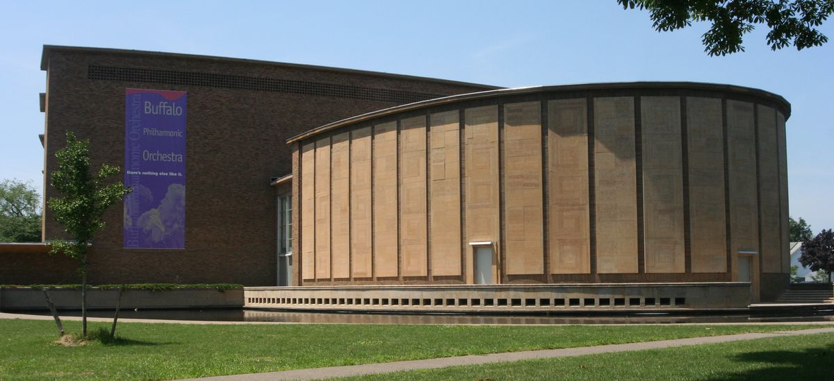 The exterior of the Kleinhans Music Hall in Buffalo, New York. The facade is brown brick with a curved shape. There is a banner hanging with words that read: Buffalo Philharmonic Orchestra.