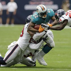 Miami Dolphins running back Reggie Bush (22) pulls three Houston Texans defenders, Johnathan Joseph (24), Danieal Manning (38) and Glover Quin, left, for a first down in the first quarter of an NFL football game on Sunday, Sept. 9, 2012, in Houston.