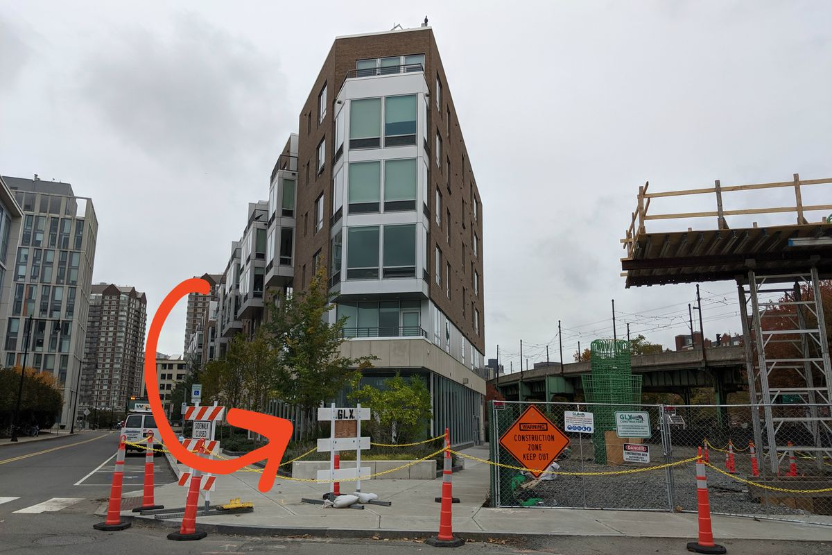 The exterior of a triangular building, with an overlaid red arrow pointing to a construction site on the ground floor that will become a restaurant