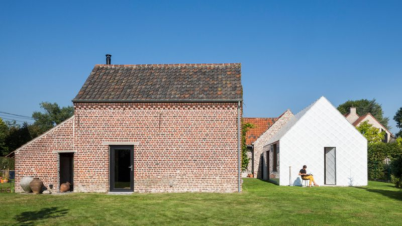 Brick house next to white garden shed.