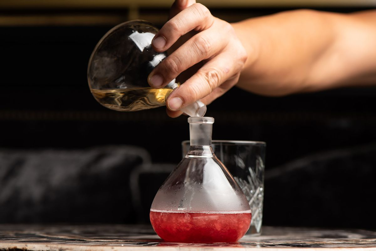Two cocktail ingredients being poured into a beaker at a bar.