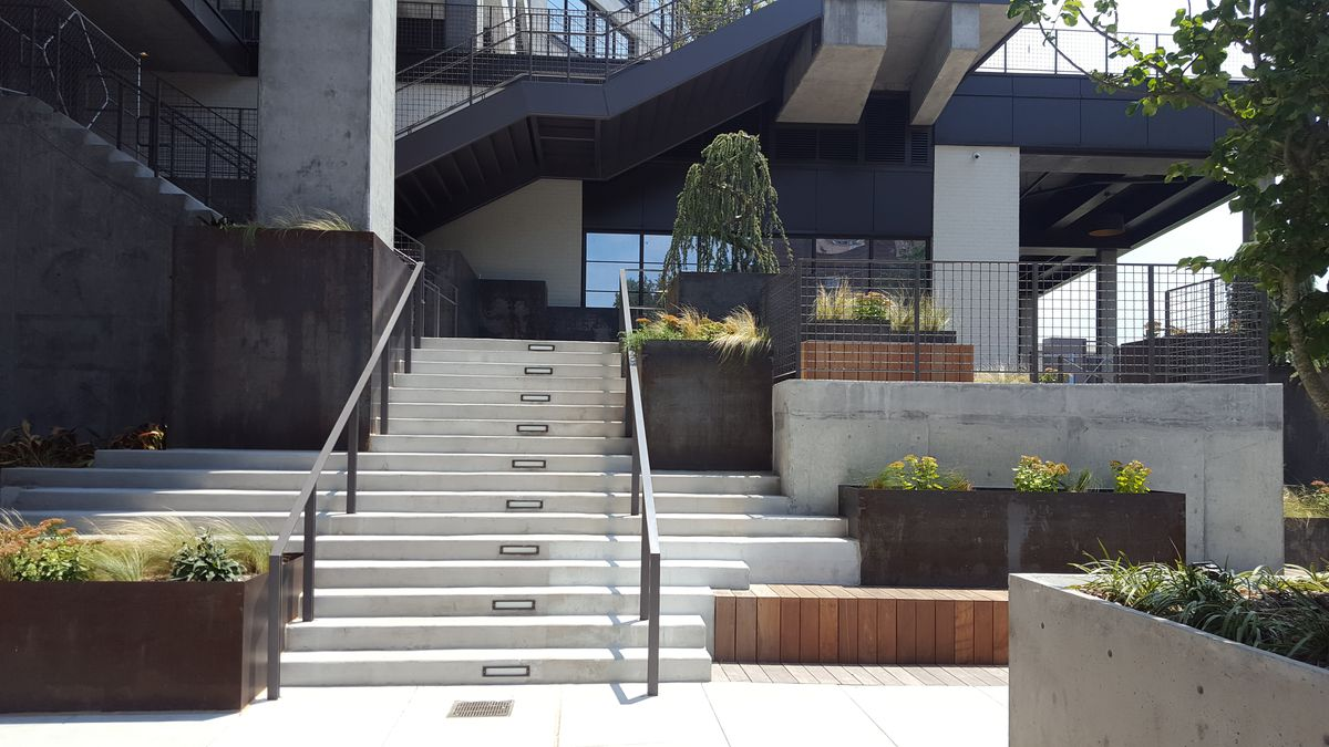 A grey staircase in the pedestrian plaza is surrounded by metal planters and greenery.
