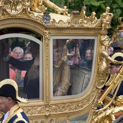 Netherlands' King Willem-Alexander and his wife Queen Maxima, at the window right, wave to well wishers as they arrive at Noordeinde Palace, after the King officially opened the new parliamentary year with a speech outlining the government's plan and budget policies for the year ahead in The Hague, Netherlands, Tuesday, Sept. 17, 2013.