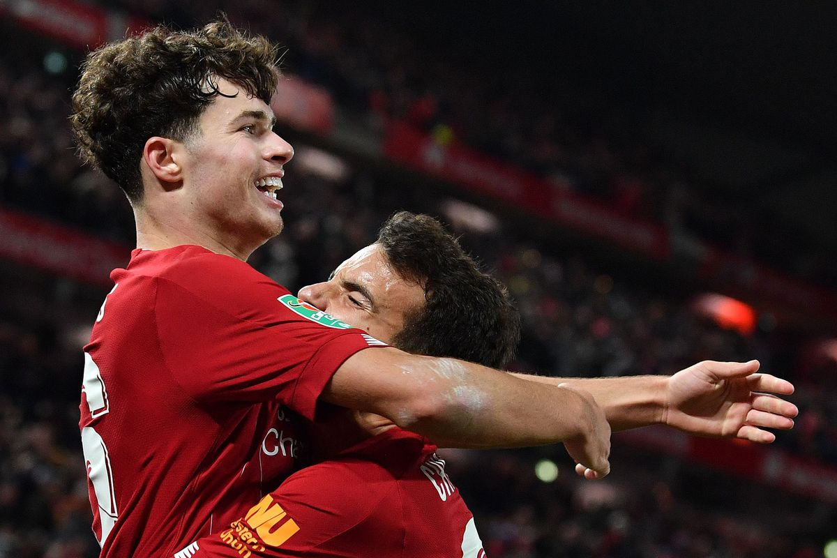 Liverpool's Spanish midfielder Pedro Chirivella (R) congratulates Liverpool's Welsh midfileder Neco Williams for crossing the ball to let Liverpool's Belgium striker Divock Origi (unseen) score his team's fifth goal during the English League Cup fourth round football match between Liverpool and Arsenal at Anfield in Liverpool