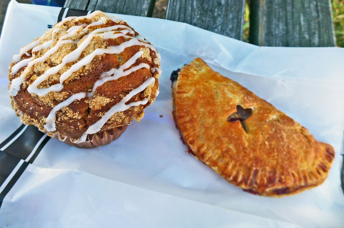 A muffin on the left with squiggles of white icing on top and on the right a fried pie with a cross cut on top to let steam escape.