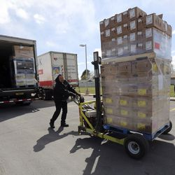 Tyson Hyde, Utah Food Bank driver, moves pallets of food to hand out in the parking lot of a chapel belonging to The Church of Jesus Christ of Latter-day Saints in Taylorsville on Monday, April 13, 2020. The Utah Food Bank estimates it provided food to around 400 families at this location.