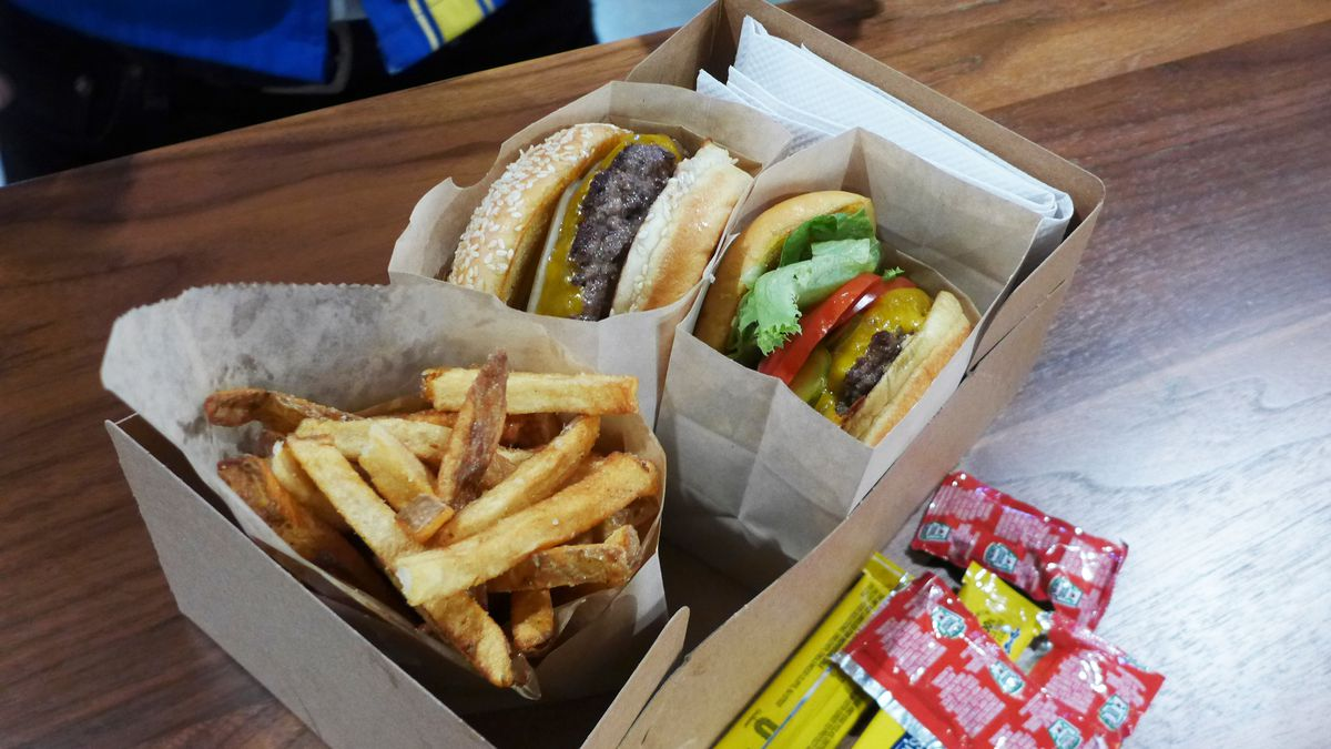 Two burgers in boxes, one with salad stuff on it the other without, on sesame seed buns with french fries on the side.