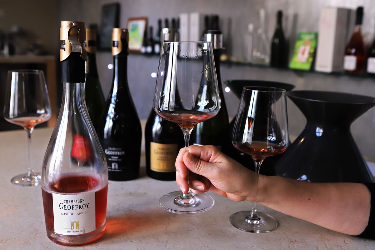 On a table, there's a bottle of Rene Geoffroy rosé de saigné on along with two glasses holding tastes of the wine and a hand lifting up one of these glasses
