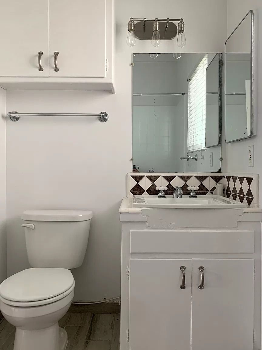Bathroom with cabinet above toilet.