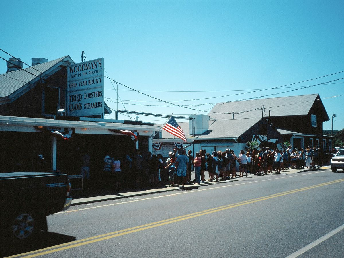 a long line of people outside of a casual seafood restaurant