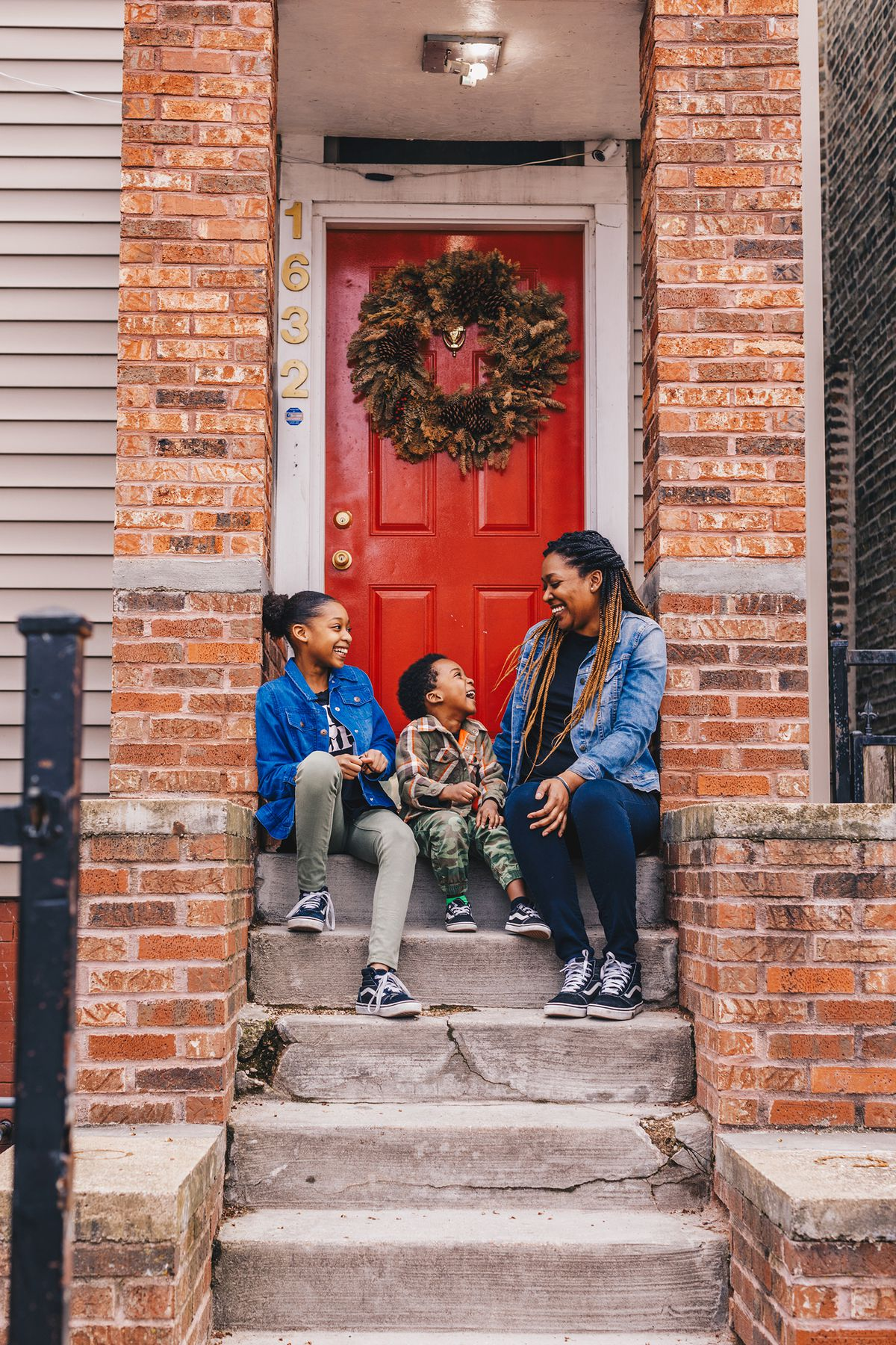 Sameka Gates and her kids, Kylee, 11, and Ethan, 5, sit on their front steps in Hermosa.