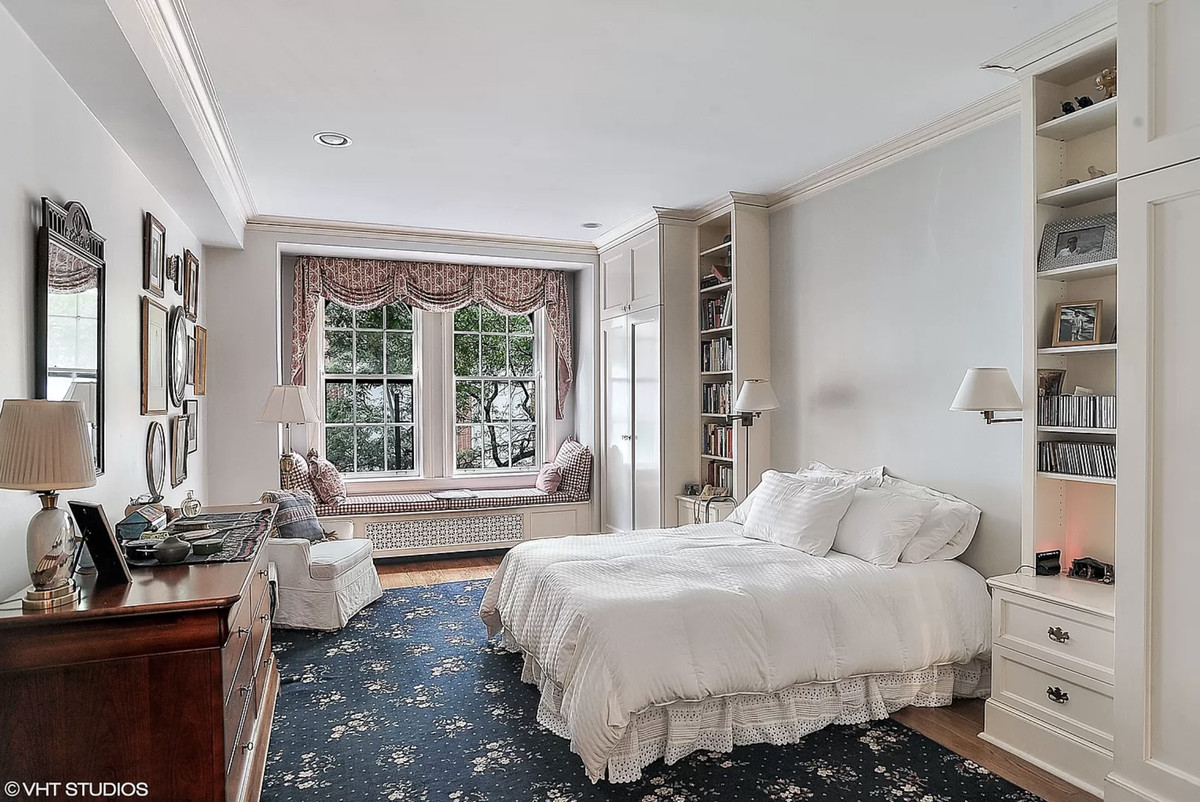 A bedroom with built-in shelving, a large window, a blue area rug, and a dresser. There is a window with a bench underneath it.