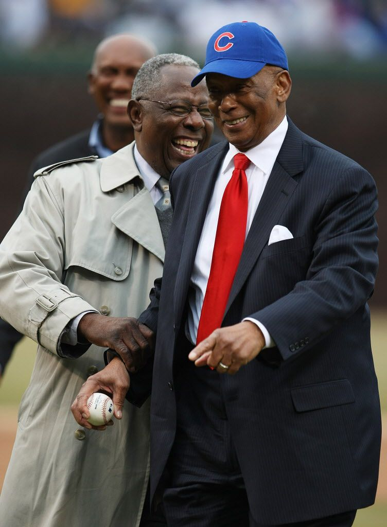 """Former Chicago Cub Ernie Banks enjoys a moment with Henry """"Hank"""" Aaron before throwing out a ceremonial first pitch before the Cubs take on the Milwaukee Brewers during the Opening Day game at Wrigley Field March 31, 2008. (Photo by Jonathan Daniel/Getty"""
