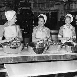 """Volunteer workers at the canning plant tackling tomatoes, June 10, 1943. The volunteers, Mrs. Wesley Tomlinson, left, Mrs. P. B. Piersanti and Mrs. Eugene E. Snyder, were all affiliates of the Ogden Elks Does that kept the plant going during the war years. The image is on display at Ogden's Union Station as part of """"Weber Works."""""""