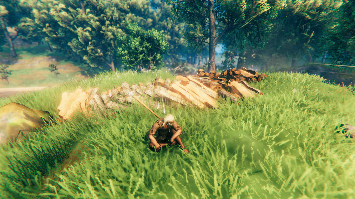 A character in Valheim sits near a massive pile of wood