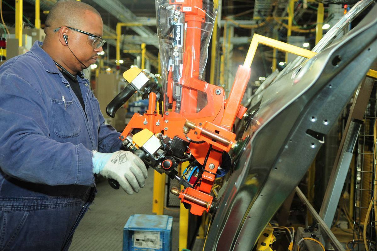 Using suction cups on an assembly line tool, a worker lifts Explorer SUV doors from a line and moves them into place for mounting.