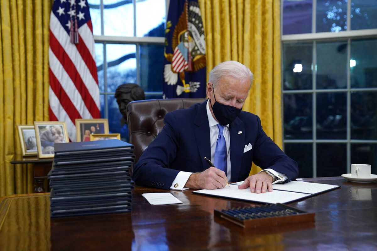 President Joe Biden signs his first executive order in the Oval Office of the White House