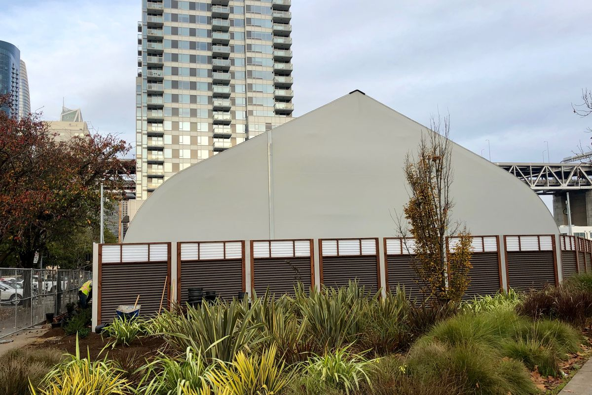 A tent-like white structure, with tall glass-covered high-rises in the background.