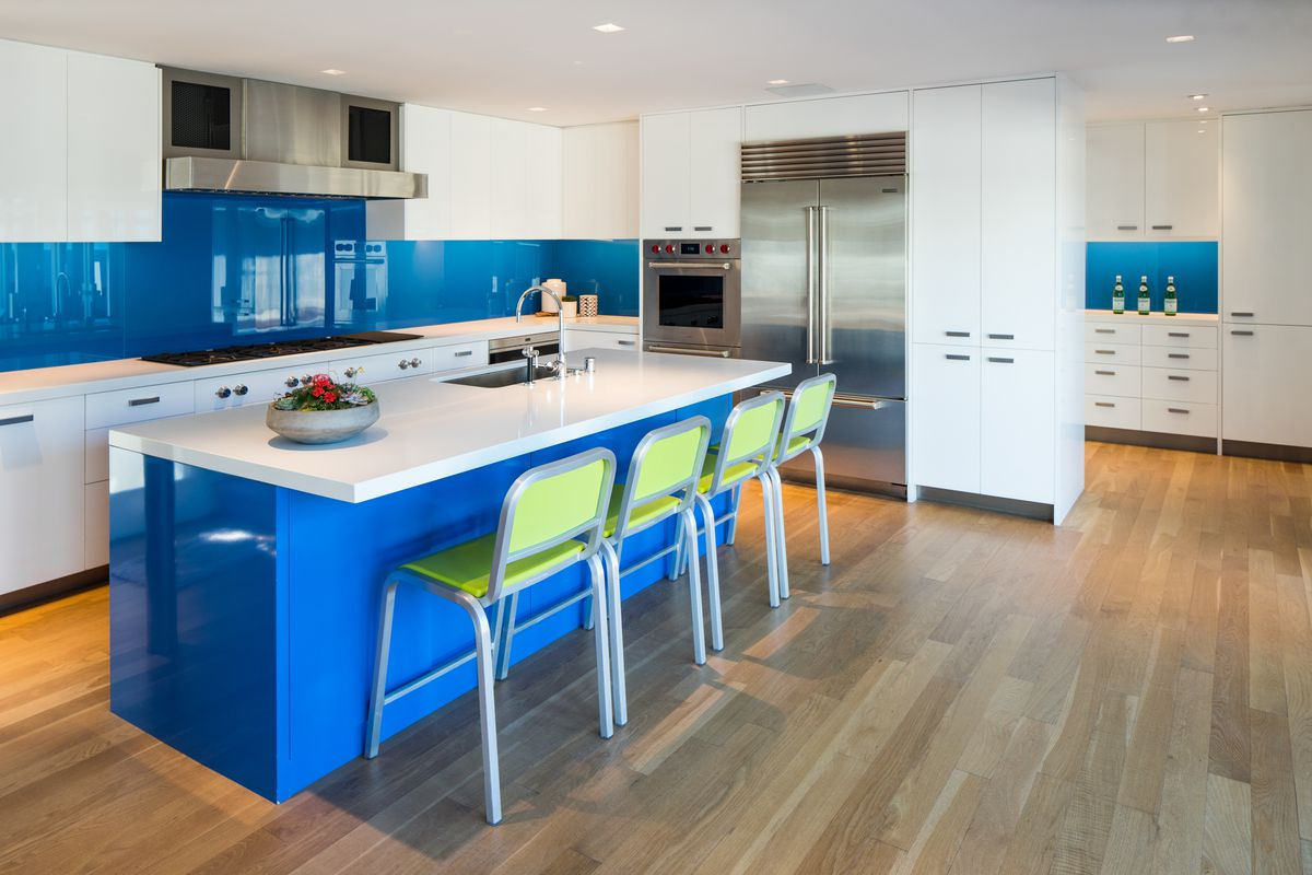 A kitchen has white counters, a blue island, and green bar stools on wood floors.