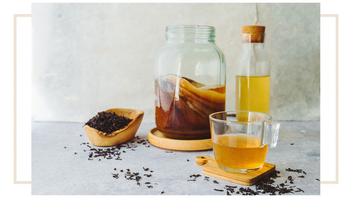 A clear glass of tea with a jar of SCOBY, a glass bottle with cork stopper, and a wooden dish of loose tea leaves.