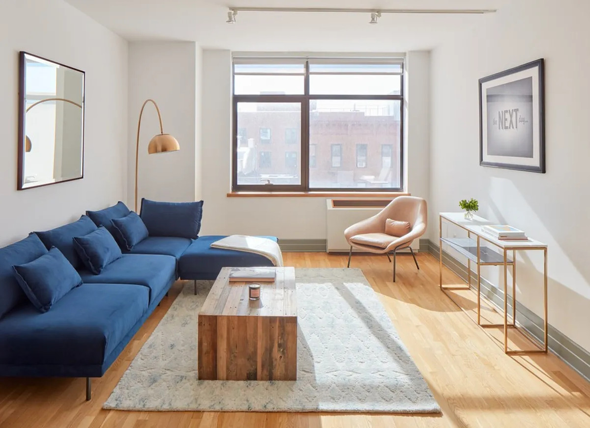 A living area with hardwood floors, beige walls, a large window, and a blue couch.