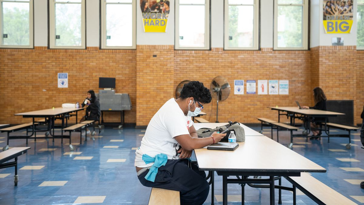 Nathaniel Martinez sits alone at a long cafeteria table. The large room, with blue tiled floors, brick walls and long windows, appears largely empty, with two students sitting by themselves at tables in the background.