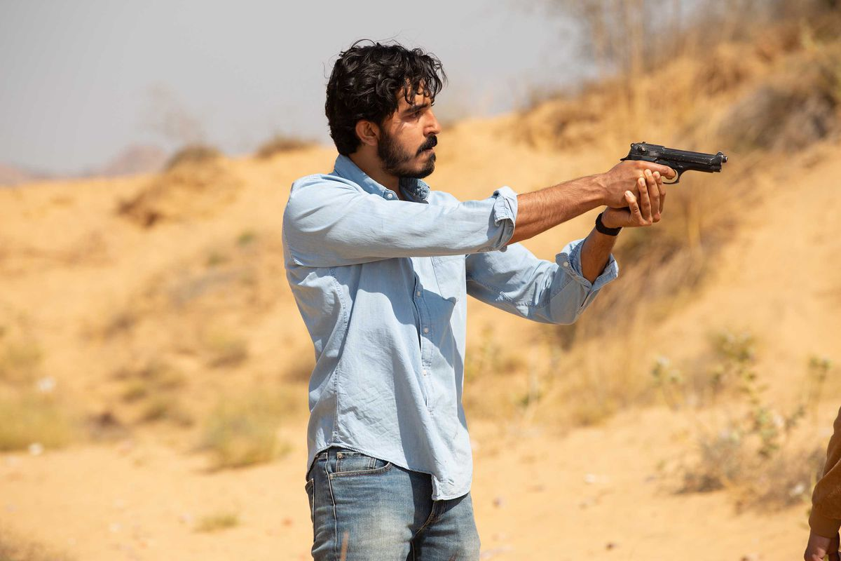 An armed Dev Patel in The Wedding Guest.