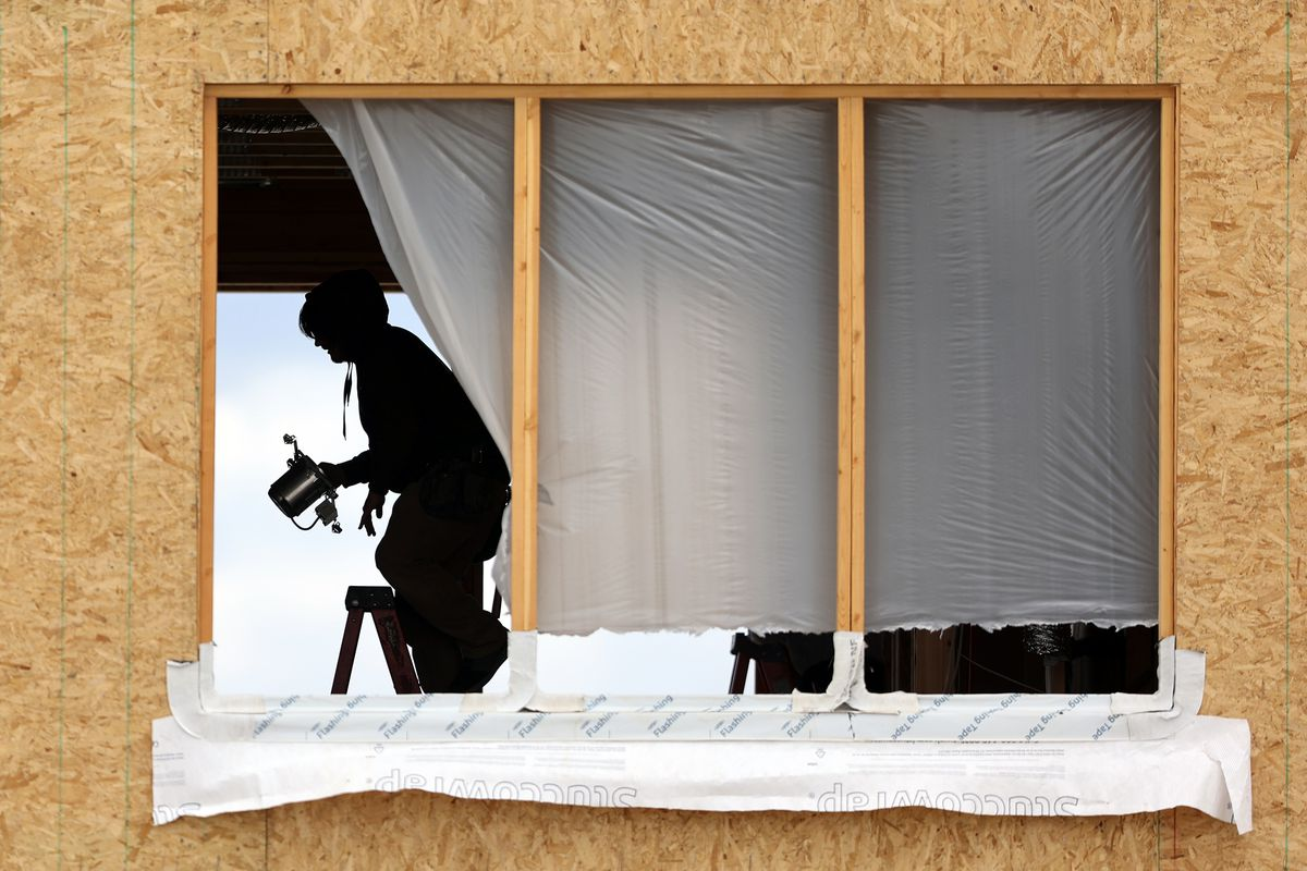 A worker installs a recessed light fixture at a building site in South Jordan on Monday, May 10, 2021. Unprecedented increases in the cost of lumber and other building supplies is driving up prices in Utah's already red-hot real estate and renovation markets.