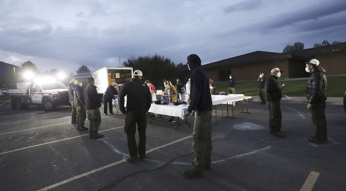 Fire crews social distance while waiting for their dinner at Midway Elementary School in Midway after fighting the Saddle Fireon Thursday May 14, 2020.