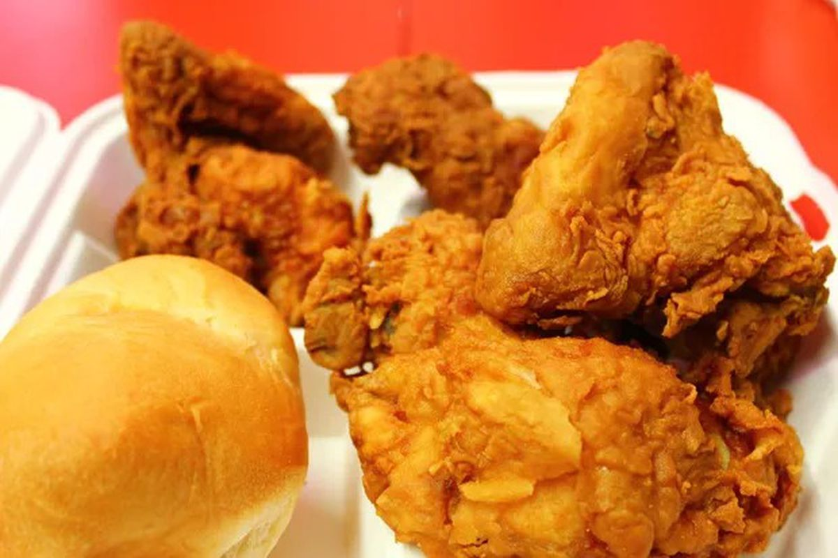 A picture of several pieces of Ezell's chicken and a roll in a styrofoam container.