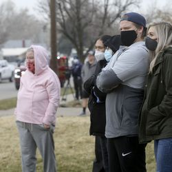 Brandi Wiley, right, and her, husband Keaton Wiley, and other onlookers watch as emergency responders work at the scene of a collision involving eight vehicles spanning the block between 300 East and 400 East on 400 North in Bountiful on Thursday, Dec. 10, 2020. A dump truck hit a power pole and seven vehicles, some vacant and parked, leaving four people injured.