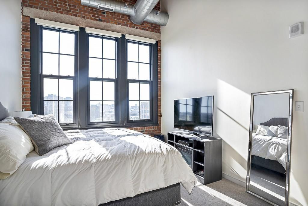 A bedroom with high ceilings, big windows, and a bed.