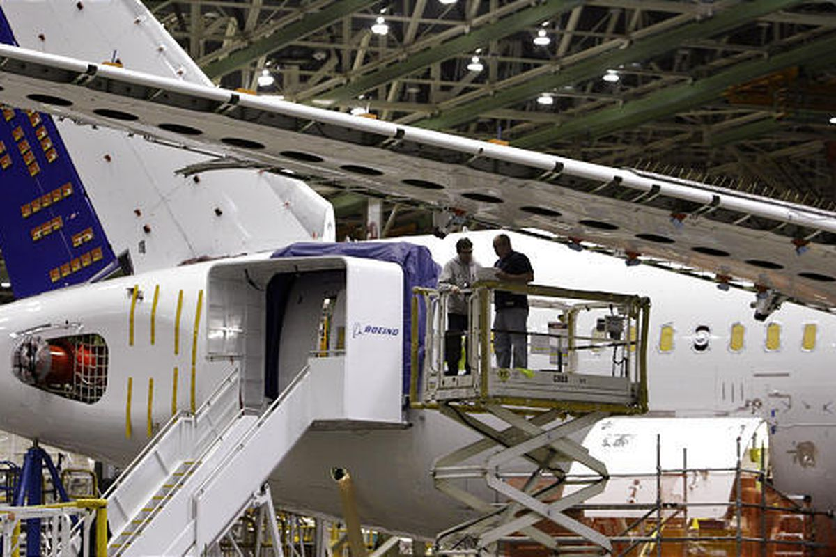 Boeing employees work near a wing on a 787 fatigue test airplane last April at the plant in Everett, Wash.