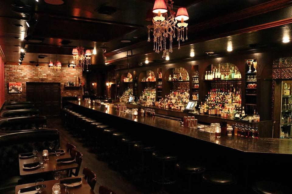 A very dark bar with a back bar lit up.