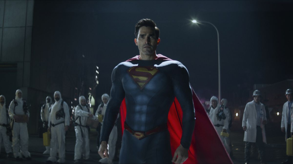 Tyler Hoechlin in his Superman costume stands in front of a group of hazmat-suited workers at night in Superman & Lois