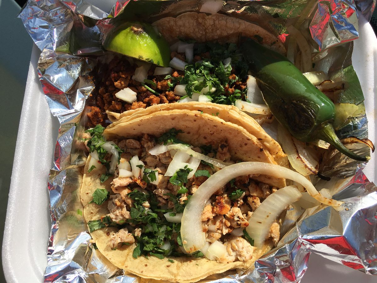 Tacos in a takeout container lined with foil and surrounded by white onions and grilled jalapenos.