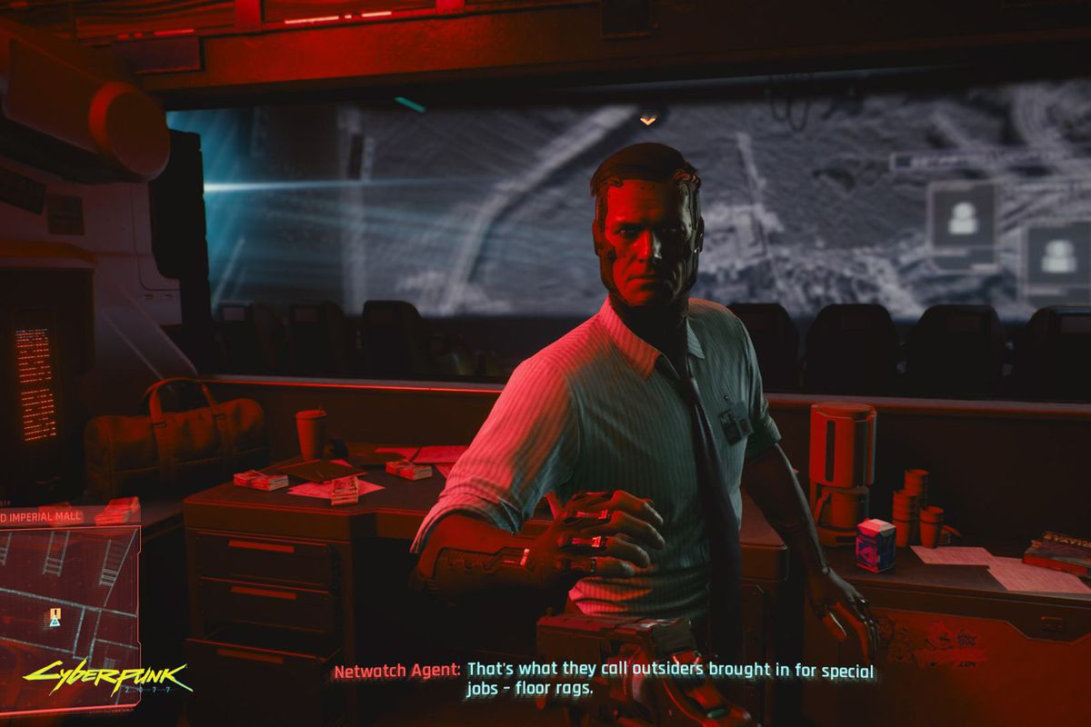 Cyberpunk 2077, E3 2019 - An agent of the Netwatch, dressed in a collared shirt and tie with his nametag clearly visible. He's holed up in the projection room of a movie theater, protected by Animals, during the demo shown to the press at E3 2019.
