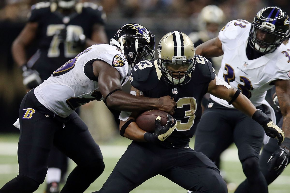 NEW ORLEANS, LA - Pierre Thomas #23 of the New Orleans  Saints is brought down by Matt Elam #26 of the Baltimore Ravens during the third quarter of a 2014 game at the Mercedes-Benz Superdome.